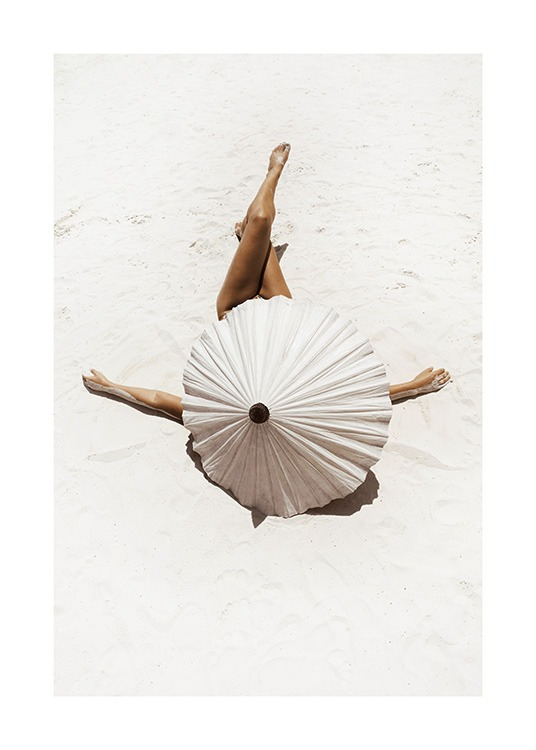 – Photograph of a woman covered by a beige parasol, laying on white sand with her legs crossed