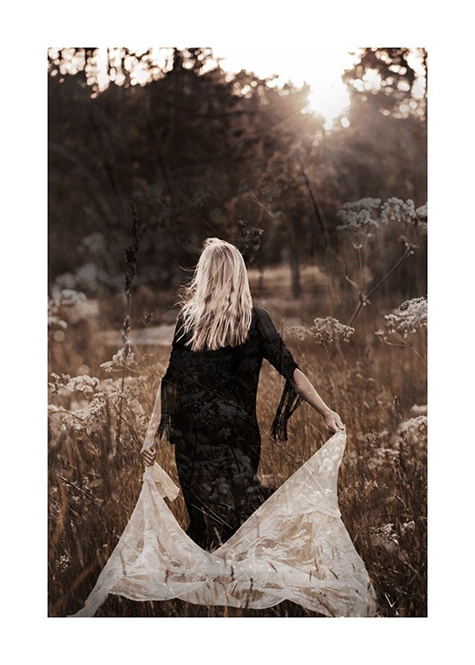 – Photograph of a woman walking in a field in a black dress, holding white lace behind her