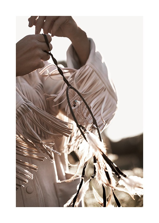 – Photograph of a woman with a jacket with fringes, holding a dreamcatcher in the sunlight