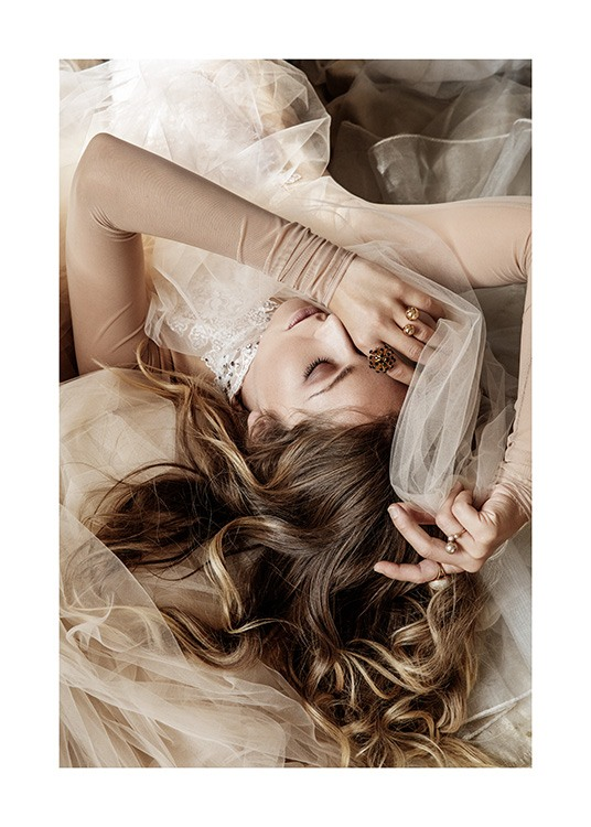 – Photograph of a woman in a beige shirt, laying in a pile of white and beige tulle