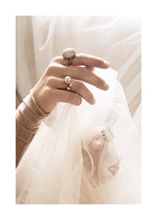 – Photograph of a woman with rings on her fingers, holding white tulle fabric in her hands
