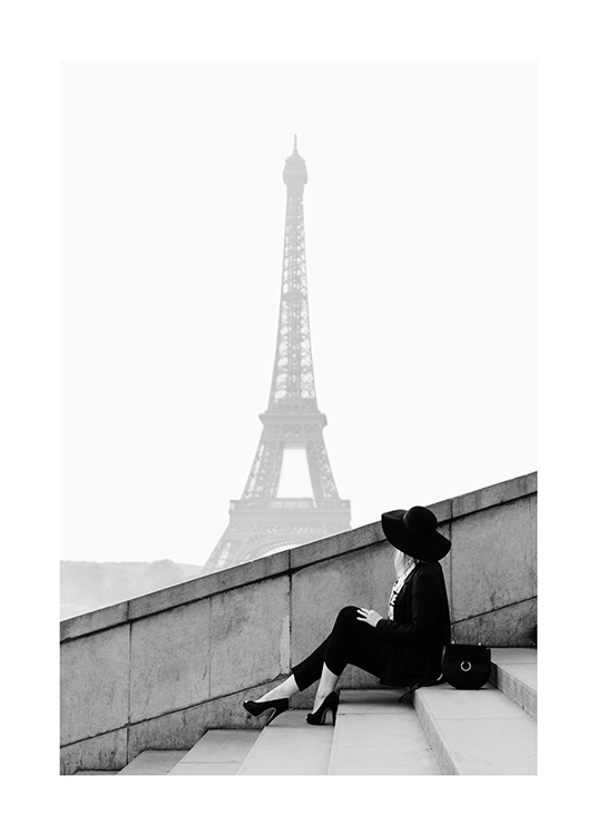 – Black and white photograph of a woman sitting on a staircase with the Eiffel Tower in the background