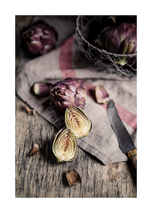 – Photograph of sliced pieces of artichokes and a knife laying on a linen cloth on a wooden table