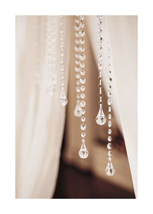 – Photograph with close up of a bunch of crystal pendants with white curtains behind them