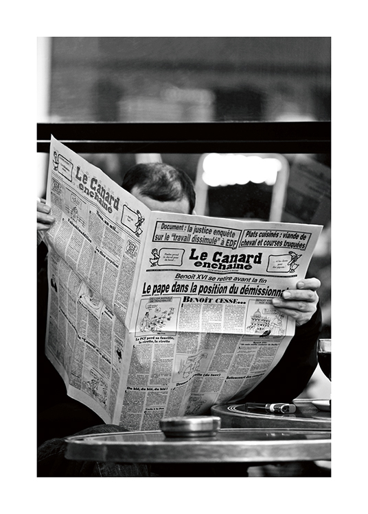 – Black and white photograph of a man reading a newspaper with the title Le Canard enchainé
