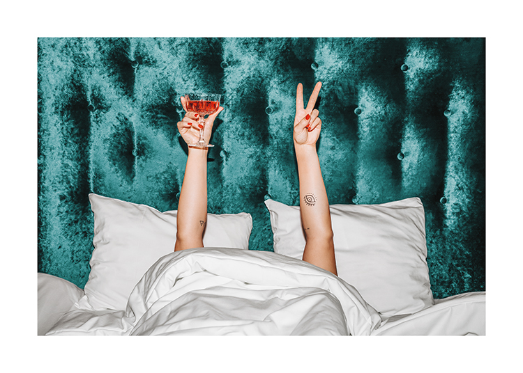 – A woman holding an orange drink in a bed with a turquoise velvet headboard