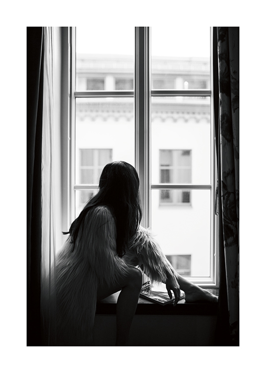 – A black and white photo of a dark-haired woman sitting on a windowsill in a faux-fur jacket