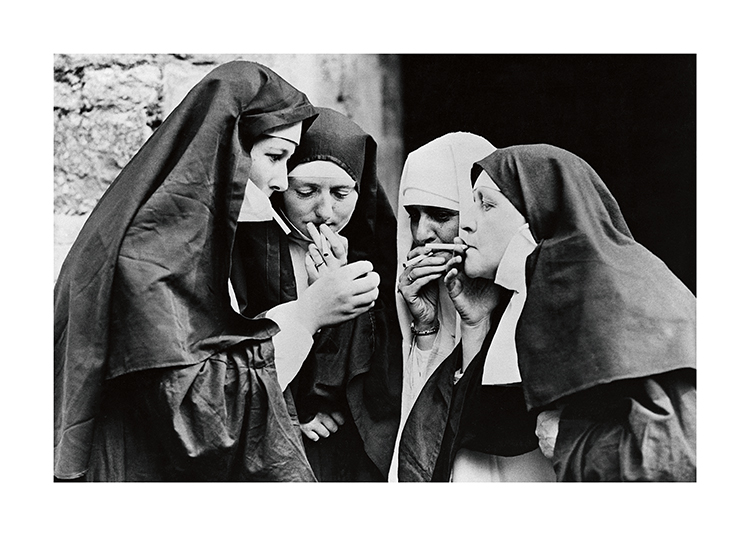 – Black and white photograph of nuns standing in a group and smoking