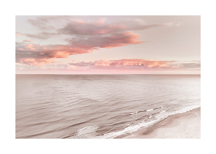 – Photograph of pink and orange clouds in the sky behind a still ocean