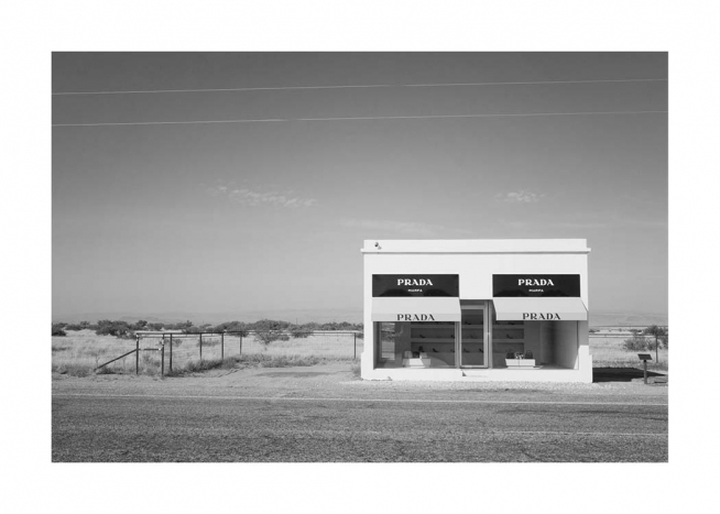 - Black and white photograph of the fake Prada Marfa Shop that's located along a road in the desert in Texas