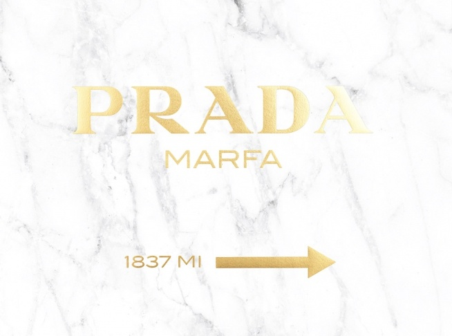 – Prada Marfa sign with text and an arrow in gold on a white marble background