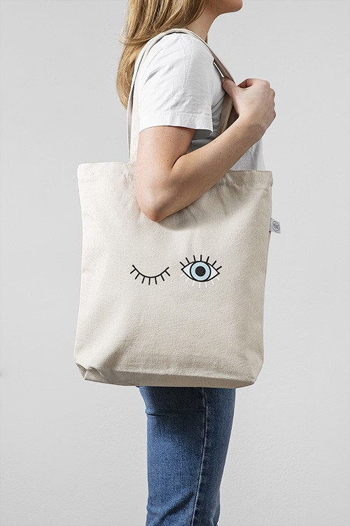 – Beige tote bag with an open, blue eye and a closed eye on the front
