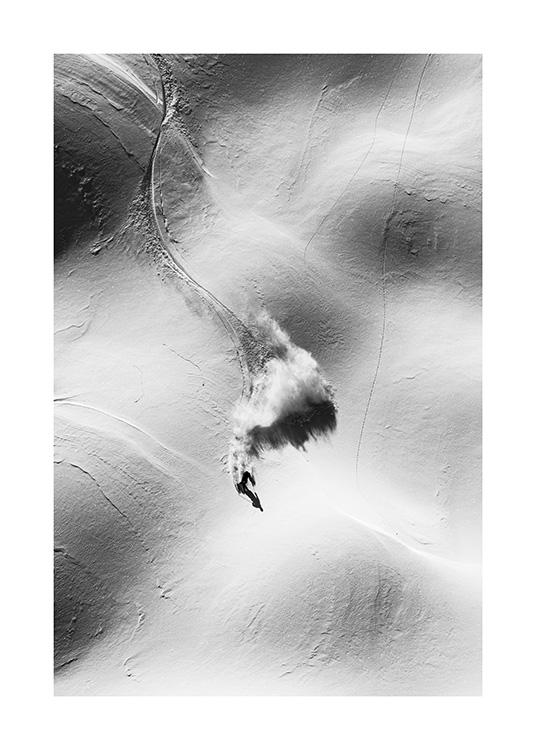 - Black and white photograph of a skier from above going through a hilly landscape